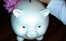 picture of small child placing money into a white piggy bank
