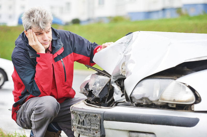 man in red and blue jacket looking at damaged front of car