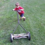 Small boy pushing manual lawn mower