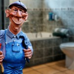 Plumbing contractor holding a plunger for toilet and pipe wrench smiling inside a bathroom