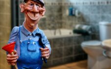 Handyman contractor holding a plunger for toilet and pipe wrench smiling inside a bathroom