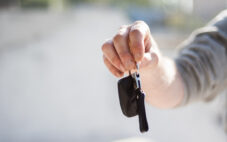 Person holding arm extended with car keys in hand