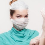 Doctor in surgery gear with face mask and plastic gloves on