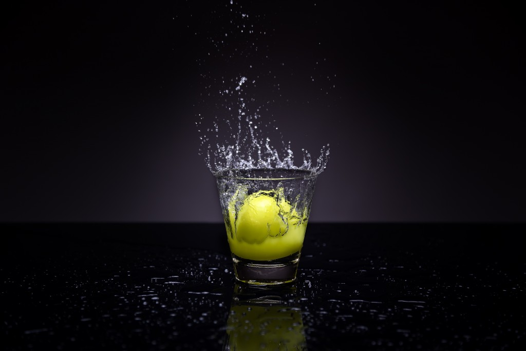 Lemon splashing into glass full of water
